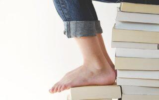 Füsse auf einem Stapel Bücher als Visualisierung für einen Grundlagenkurs für ITIL 4 Foundation