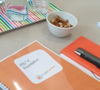 Hier sollten Sie ein Bild eines Kursplatzes mit Handout, Schreibgeräten und Getränken und Snacks bei einem ITIL 4 Foundation Kurs bei ITSM Partner sehen.